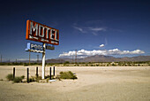 The sign of a failed and long-since destroyed motel stands ironically alone beside empty ground a desert highway in Yucca, Arizona, USA.