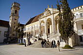 Coimbra, Portugal: Students in the inner core of the University of Coimbra in front of steps leading to cloistered arcade, Via Latina. The University was established in 1537. Note the famous curfew-signaling clock of Coimbra...