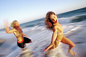 Action, Activity, Adult, Adults, Amusement, Bathing suit, Bathing suits, Beach, Beaches, Bikini, Bikinis, Blurred, Caucasian, Caucasians, Chase, Chasing, Coast, Coastal, Color, Colour, Contemporary, Couple, Couples, Daytime, Emotion, Emotions, Exterior,