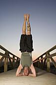 Man Doing Headstand on Footbridge