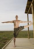 Man Stretching on a Wooden Platform