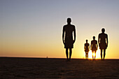 Adult, Adults, Back-light, Backlight, Beach, Beaches, Color, Colour, Contemporary, Daytime, Evolution, Exterior, Figure, Figures, Four, Four persons, Full-body, Full-length, Future, Horizon, Horizons, Horizontal, Human, Humanity, Isolated, Isolation, Mal