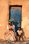 Traditionally dressed Herrero woman and grandson at their house. Warmquelle village. Southern Kaokoveld. Namibia
