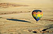 The hot-air balloon above eroded landscape at the edge of the Namib Desert. Namib-Naukluft Park, Namibia.