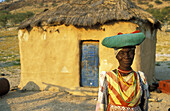 Traditionally dressed Herero woman at her house in the vicinity of Warmquelle, a village in the southern Kaokoveld. Namibia.