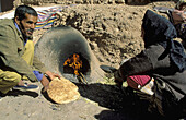 A Berber woman bakes bread at a public square inside the kasbah (fortress) Taourirt in the town of Ouarzazate, south of the High Atlas mountains. Southern Morocco.