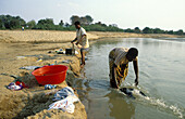 Washing clothes in the Luangwa river just opposite to the South Luangwa National Park. Zambia.