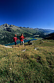 young couple hiking in alpine pasture high above lake Silvaplaner See and Champfer (Champfér) See, Engadin, Grisons, Switzerland