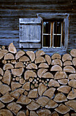 Stack of fire wood under a window of Alpine hut, Wilder Kaiser, Kaiser mountain range, Tyrol, Austria