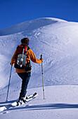 Woman backcountry skiing with avalanche shovel at backpack, Chiemgau Alps, Upper Bavaria, Bavaria, Germany