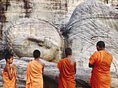 Monks praying at dawn in Gal Vihara temple, Polonnaruwa. Sri Lanka