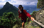 Man climbing onto Mt. Gower, Lord Howe Island, Australia