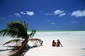 A couple sunbathing at South End Beach on West Island, Cocos Islands, Australia
