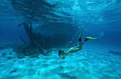 Woman diving to sunken barge, Horsburgh Island, Australia