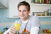 Young man holding a glass of orange juice, Munich, Germany