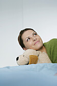 Young woman holding a stuffed dog lying on bed, Munich, Germany
