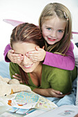 Girl (3-4 years) covering mother's eyes, Munich, Germany