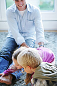 Father playing with children (2-4 years) on floor, Munich, Germany