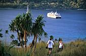 A couple walking along the coast, Blue Lagoon with MV Reef Escape off Sawa-i-Lau, Yasawa group, Fiji, South Sea