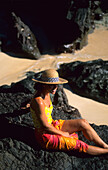 Woman relaxing, sitting on a rock on the beach, Navadra Island, Mamanuca group, Fiji, South Sea