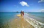 A couple walking along the beach, Sandy Point on Brampton Island, Whitsunday Islands, Great Barrier Reef, Australia