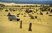 Camper van travelling through, the limestone columns of the Pinnacles, Nambung National Park, Western Australia, Australia