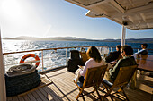 Women and men resting and reading on the sundeck of a yacht, Scottish coastline in the background, Scotland, Great Britain