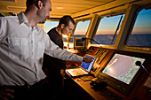 Captain and helmsman in training on the bridge of a ship, Hanse Explorer, in the evening light, Great Britain