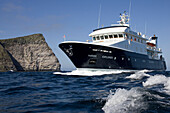 The yacht, ship, Hanse Explorer and the cliffs of the island Noss, Shetland Islands, Scotland, Great Britain