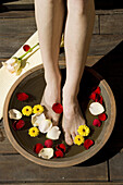 Adult, Adults, Barefeet, Barefoot, Basin, Basins, Bathe, Bathes, Bathing, Body care, Bowl, Bowls, Color, Colour, Contemporary, Daytime, Delicate, Detail, Details, Exterior, Feet, Female, Flower, Flowers, Foot, Health, Health care, Healthcare, Human, One,