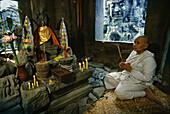 Buddhist nun praying, Bayon temple, Angkor, Siem Raep, Cambodia,  Asia