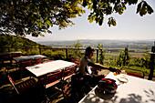 Inline speed skating champion Christoph Luginbuehl having a drink in a beer garden, near Weinfelden, Lake Constance, Switzerland