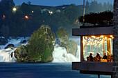 Rhine Falls at night, guests in a restaurant in foreground, Neuhausen, Canton of Schaffhausen, Switzerland