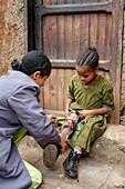 Health worker adjusting leg brace of a crippled girl in a slum of Addis Ababa, Ethiopia