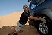 Man pushing a 4x4 vehicle, jeep out of the sand, Offroad 4x4 Sahara desert Tour, Bebel Tembain area, Sahara, Tunisia, Africa, mr
