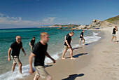 A group of men walking out of the sea, Adventure competition, North West coast, near Rena Majore, Sardegna, Sardinia, Italy, Europe, mr