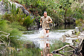 Man running through a river, adventure trail, Grabouw Forest Park, Westkap, South Africa