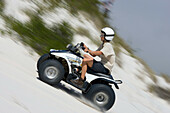 Man driving a quad up sand dunes, Atlantis Sand Dunes, South Africa, Africa, mr