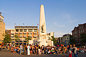 Amsterdam, Dam square at sunset people, Obelisk, background Grand Hotel Krasnaposlky