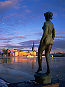 Riddarsholmen, winter view from city hall. Bronze statue of naked woman at fore. Stockholm. Sweden