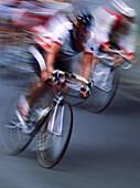 Aussen, Bewegung, Draussen, Erwachsene, Erwachsener, Fahren, Fahrrad, Fahrräder, Fahrradfahren, Farbe, Geschwindigkeit, Helm, Helme, Konkurrent, Konkurrenzfähig, Konkurrenzfähigkeit, Kopfbedeckung, Mann, Männer, Männlich, Mensch, Menschen, Mitbewerber, P