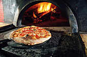 Pizza emerges from a wood buruning oven in Naples. Italy
