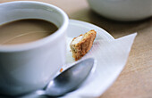 Partial view close-up of a white coffee cup and saucer with spoon and a piece of biscotti on the saucer