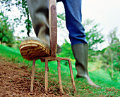 Activity, Adult, Adults, Agriculture, Boot, Boots, Color, Colour, Country, Countryside, Cultivation, Daytime, Detail, Details, Earth, Economy, Exterior, Farming, Feet, Field, Fields, Foot, Fork, Forks, Hayfork, Hayforks, Horizontal, Human, One, One perso