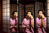 Japanese woman applies make up in a triple faced mirror in a Tokayo Hotel room. Japan
