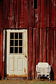 Red-brown side of barn with white painted door and folded white lawn chair, Unionville, Indiana, USA