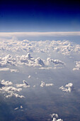 ranks of clouds seen from jet airplane, with blue sky deepening to near-black, landscape faintly visible below clouds