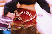 torso and arms of belly dancer, blurred with motion, another dancer s torso partially visible in background