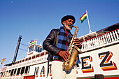 Musician playing in front of steamboat Natchez on Mississippi river. New Orleans. Louisiana, USA