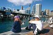 Kids having a rest. Darling Harbour. Business district. Downtown. Sydney. Australia.